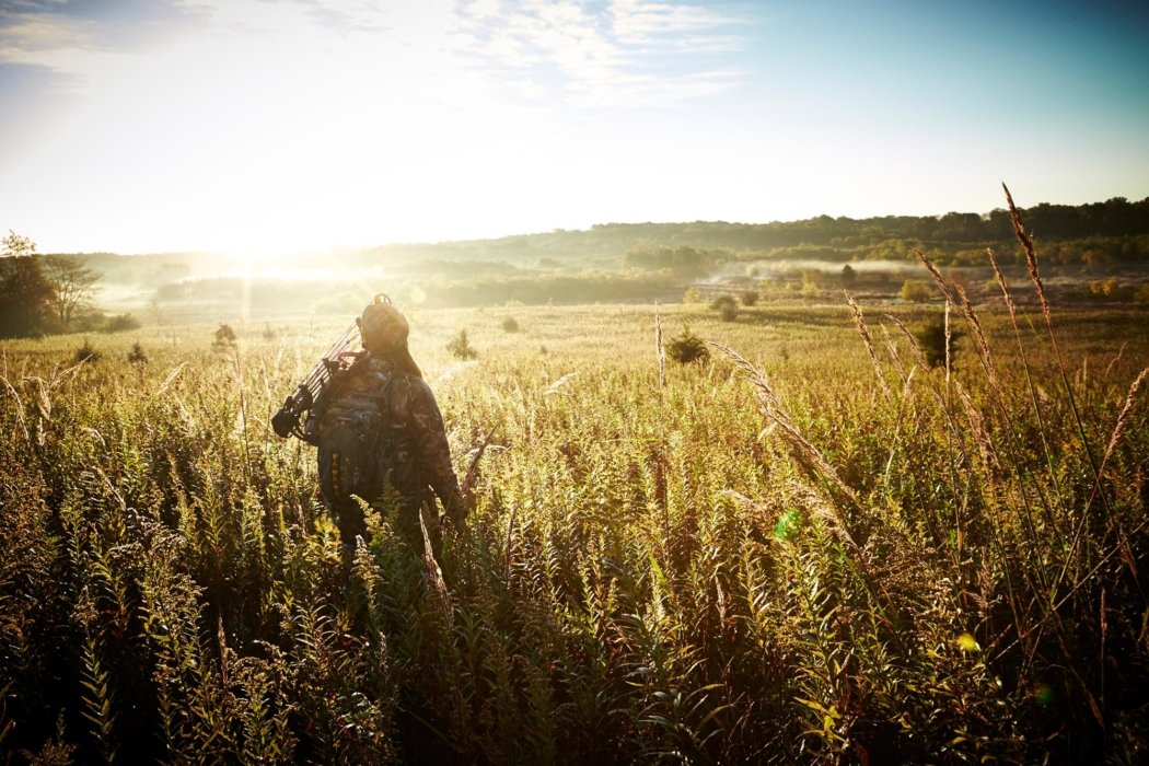 A hunter with outdoor equipment in a field