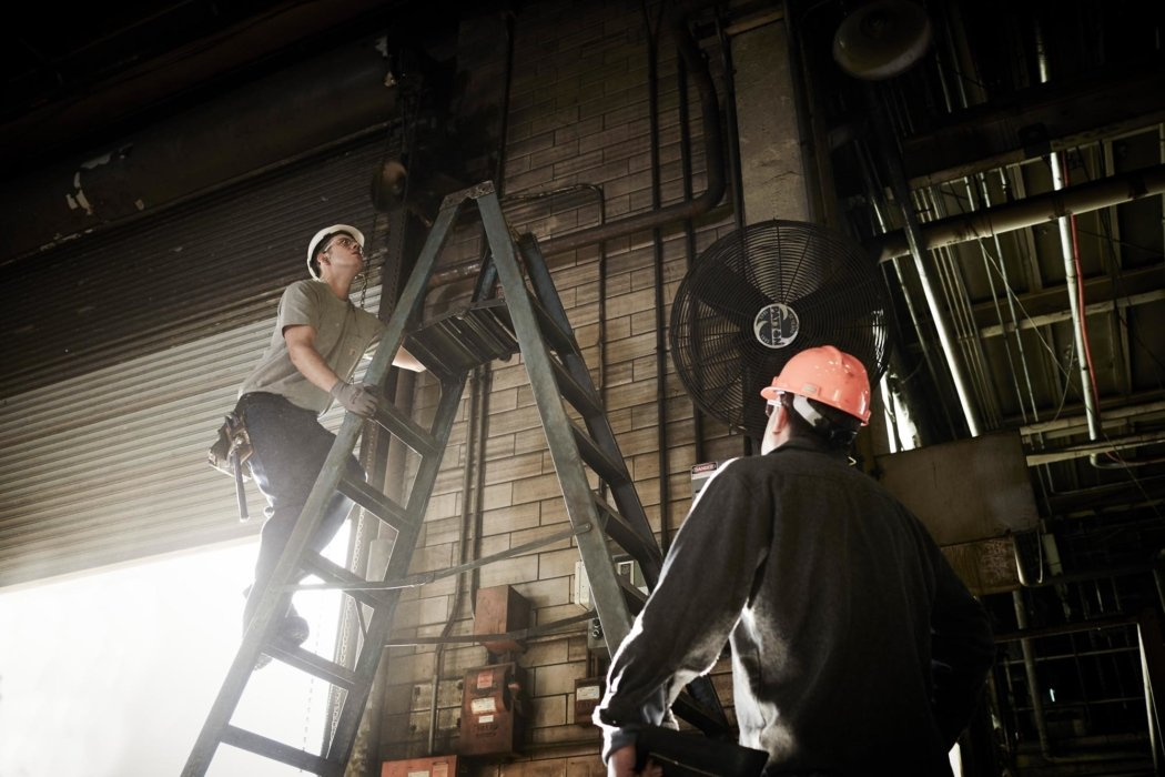 Workers on a ladder in hard hats in a facility