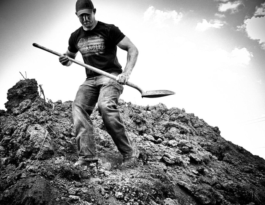 A man with a shovel walking down a hill