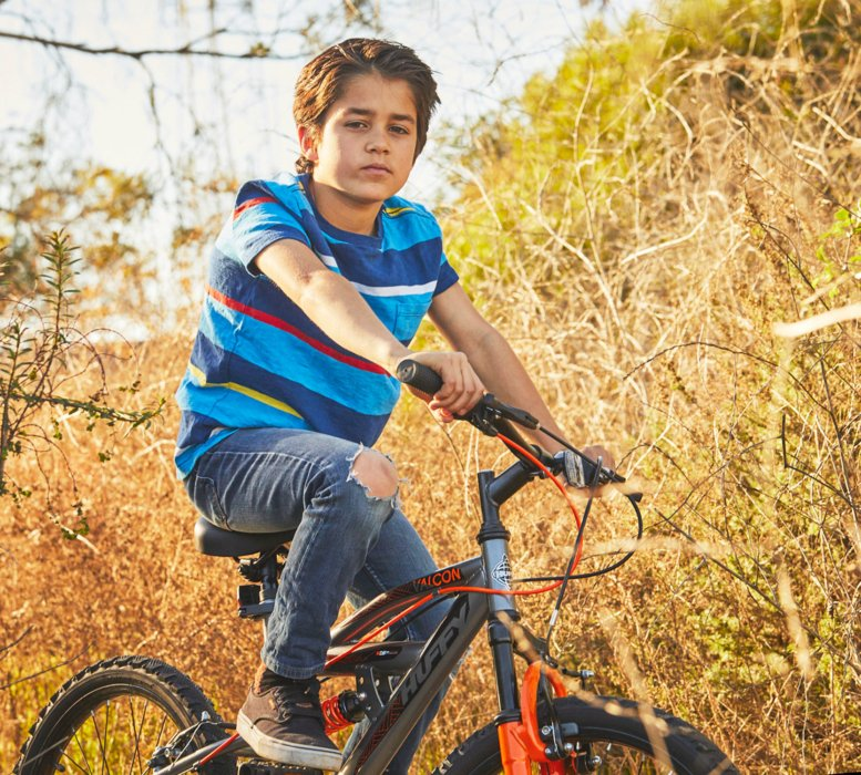 A young boy riding a bike in a grass area lifestyle - lifestyle photography