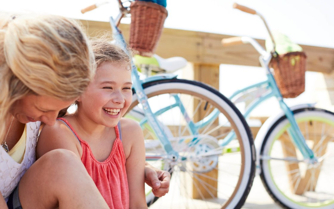 Mother and daughter laughing with bikes - lifestyle photography