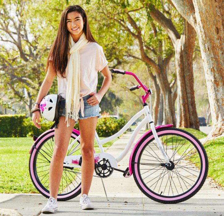 Young girl next to white and pink bike