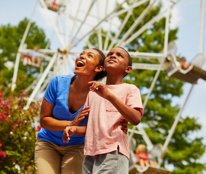 A mom and son exploring an amusement park in amazement - lifestyle photography