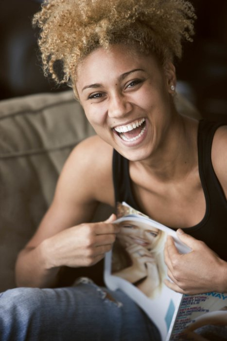 A woman laughing holding a magazine - lifestyle photography