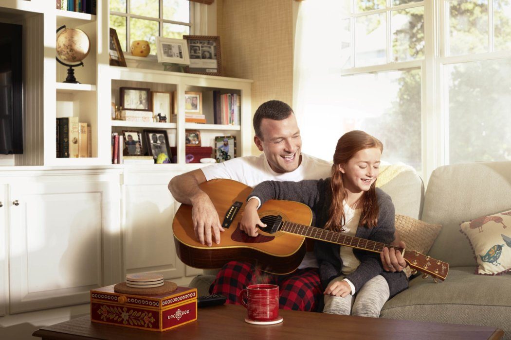 A dad teaching his daughter guitar
