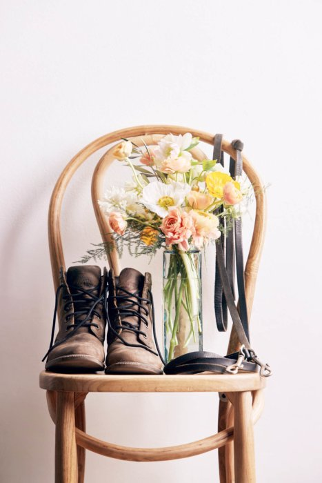 A chair with a vase of flowers and boots