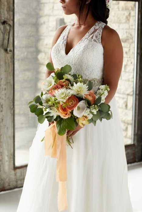 Woman holding orange and white flowers in a wedding dress