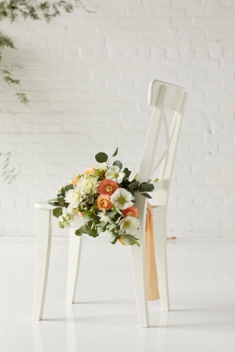Orange and white flower bouquet on a white chair