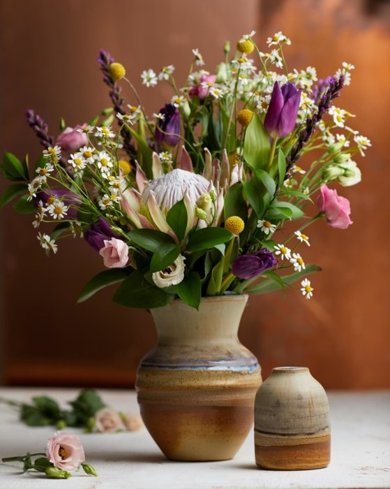 A clay vase with a spring flower arrangement