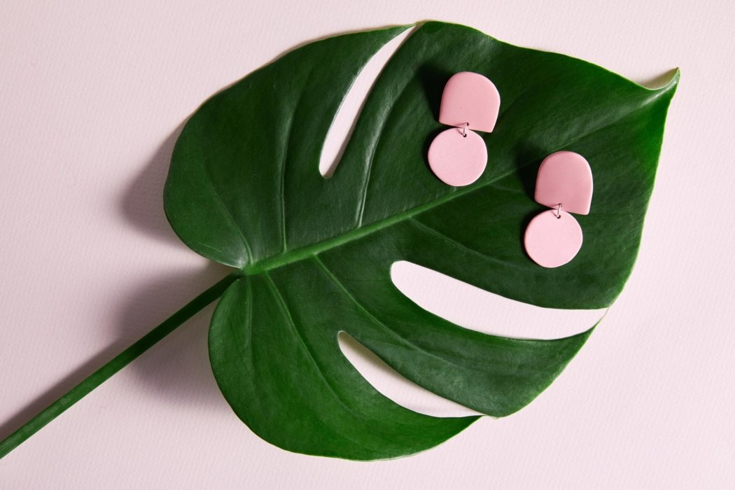 A green leaf with pink earrings on it.