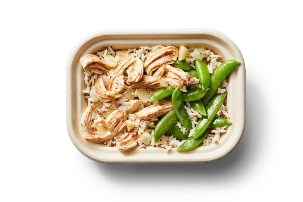 A bowl of chicken and green beans with rice on white