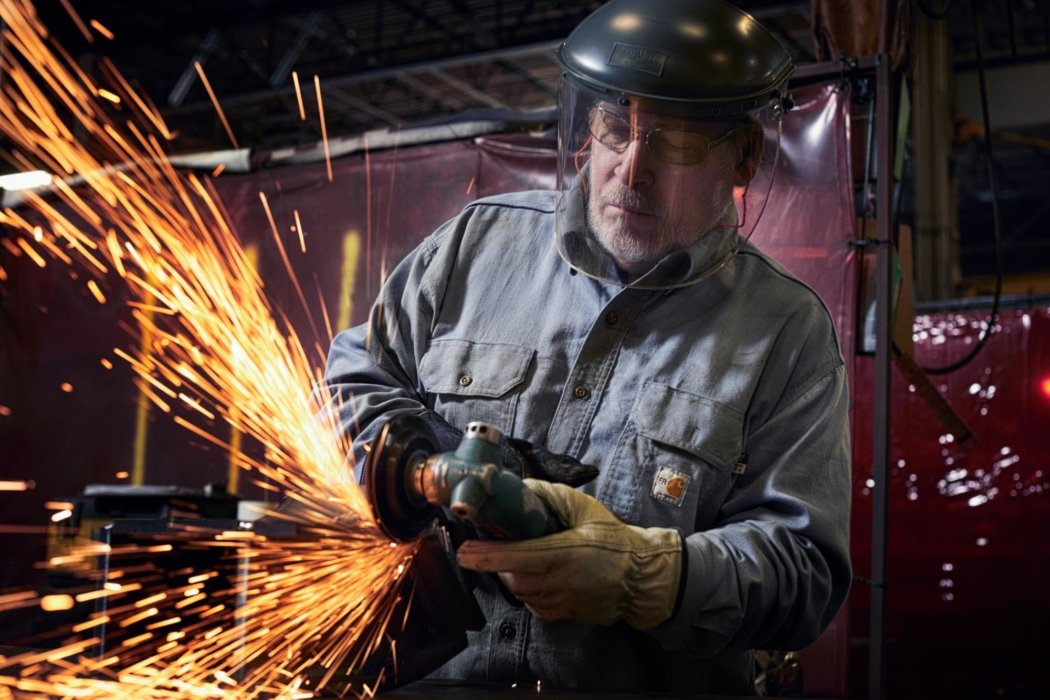 Man with welding helmet sanding metal