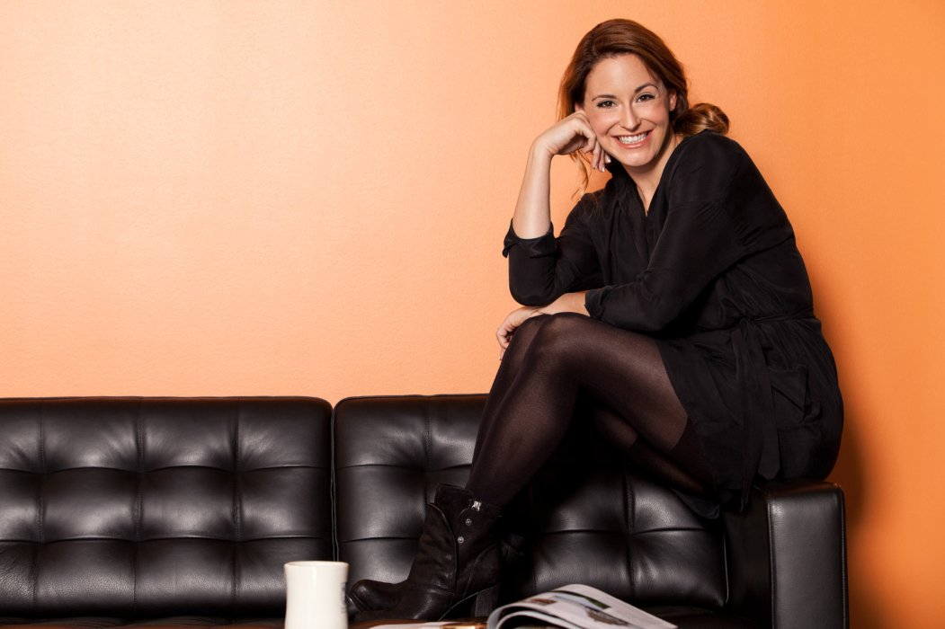 A portrait of a woman at P&G sitting on a couch