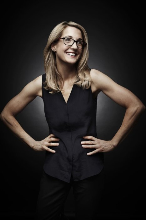 Portrait of a woman with glasses smiling with her hands on her hip on a dark background