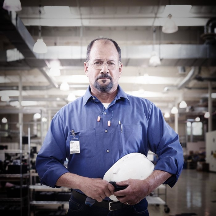 Portrait of a working man holding his white hard hat