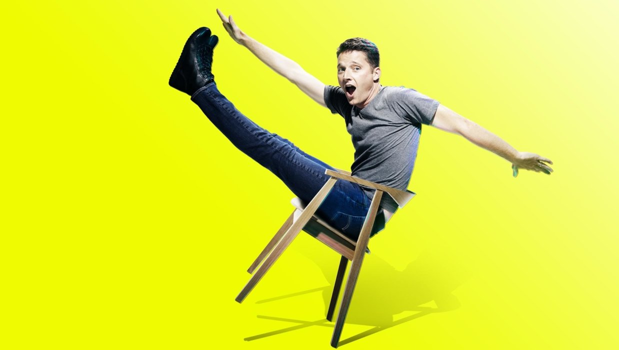 Portrait of man falling in a chair on a yellow background
