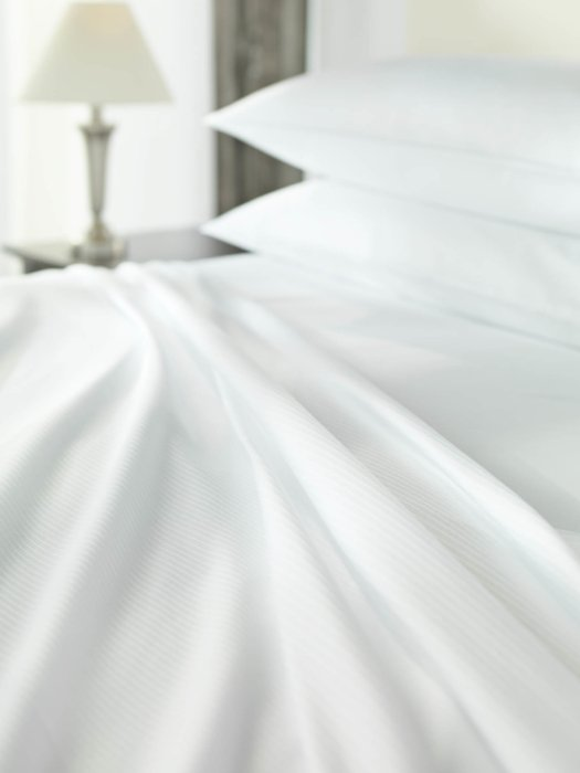 Ruffled white textile fabric bedding in a made bed