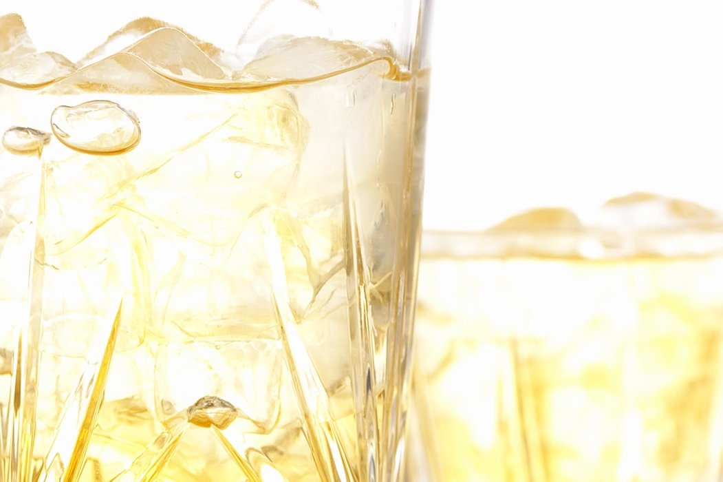 Yellow bubbling drink in a glass with ice
