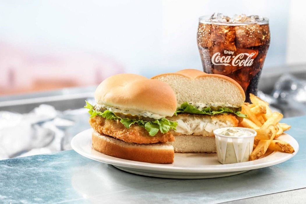 A plate of a fish sandwich with fries and coca cola