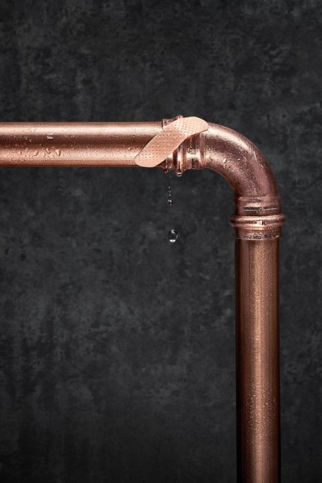 Liquid photography - a leaky copper elbow pipe being sealed with a bandage