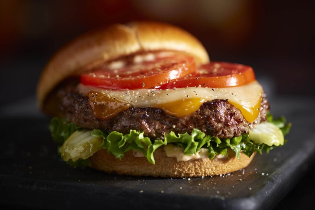Food photography - A two cheese cheeseburger with tomatoes lettuce and pickles
