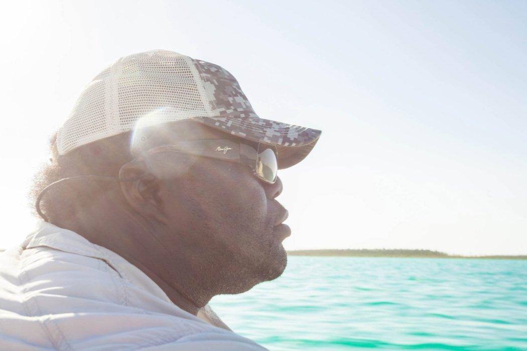 Profile view of a fisherman on a boat near the shoreline of the ocean