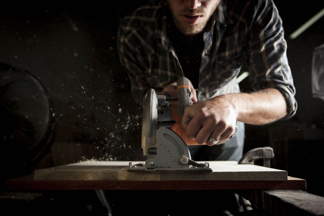 Portraits shot of a man working on wood with a circular saw