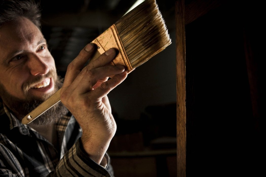 Portraits shot of a man working on wood with a paint brush