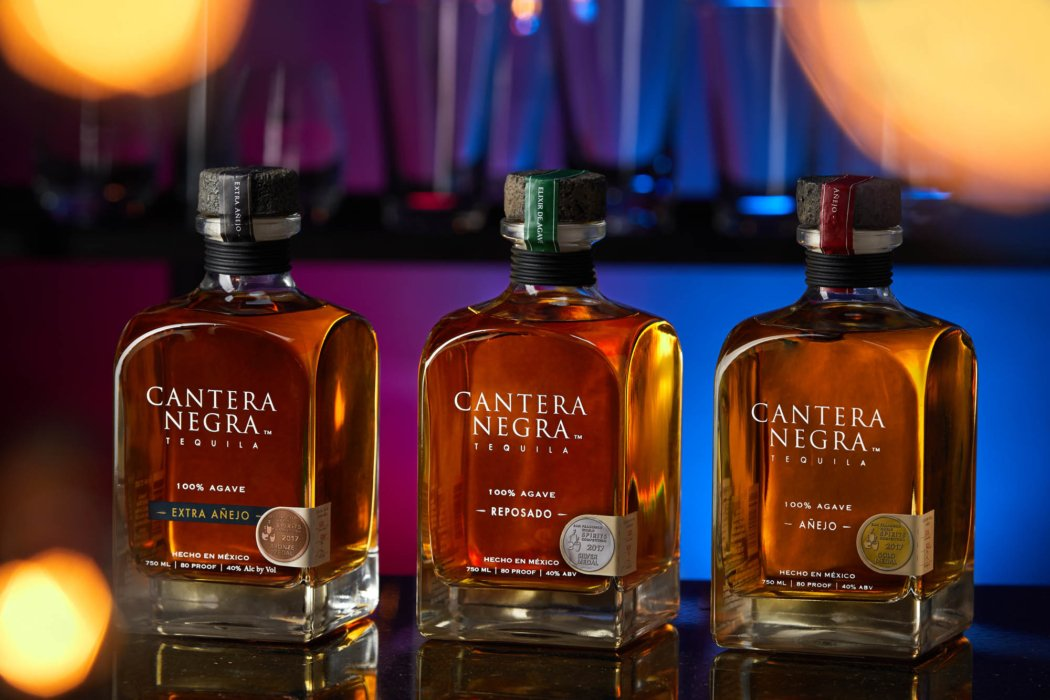 three bottles of cantera negra tequila in a bar setting