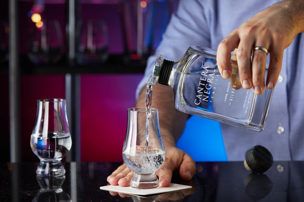 A bar tender pouring silver tequila - cantera negra - drink photography