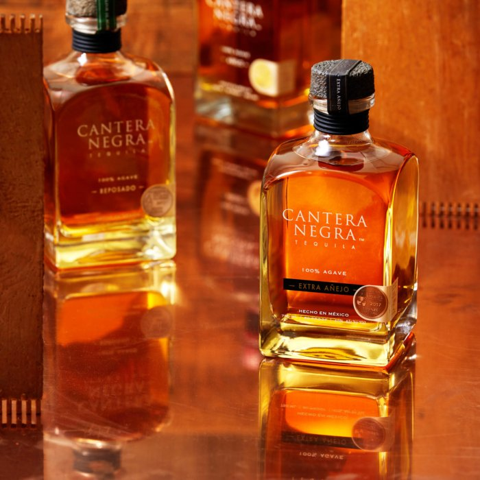 Tequila bottles surrounded by wood and copper - cantera negra - drink photography
