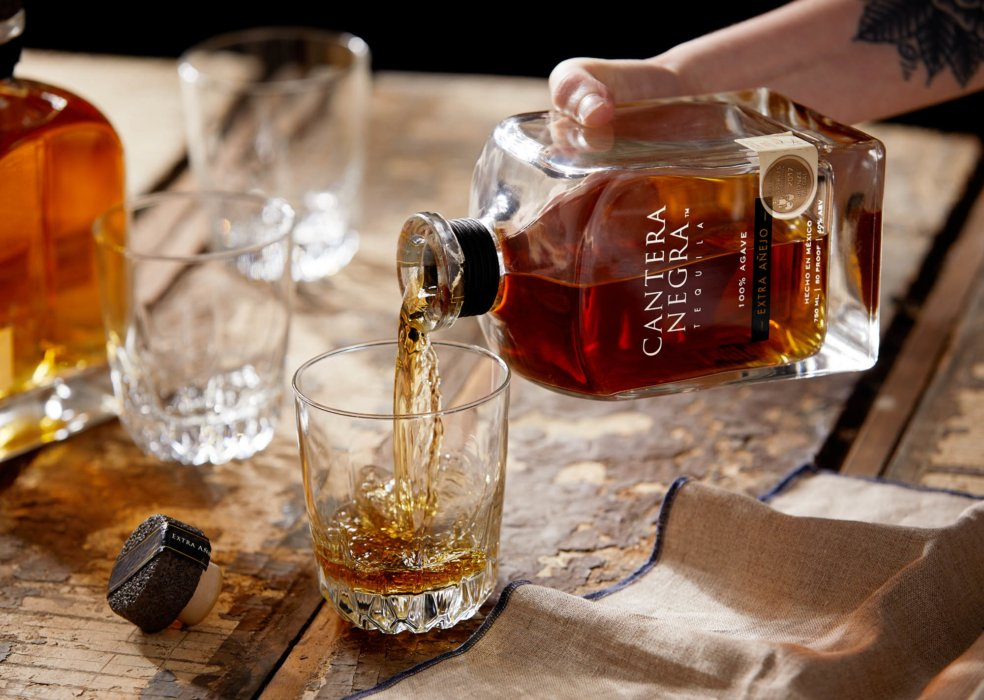 Extra añjeo tequila being poured in a modern wood setting - drink photography - cantera negra