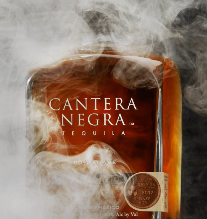 Smoke swirling around a bottle of tequila - cantera negra - drink photography