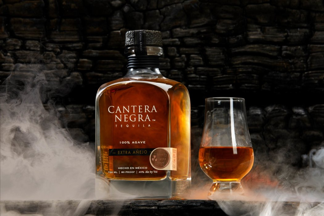 Smoke swirling around a bottle of tequila and glass on a dark wood background - cantera negra - drink photography