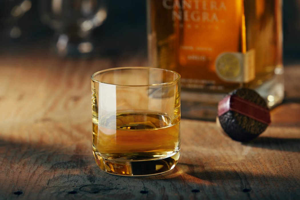 A beautiful glass of tequila on a wood surface - cantera negra -