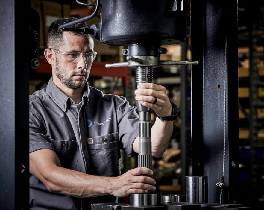A man operating a drill press n an industrial setting - A man inspecting robotic industrial equipment - industrial photography