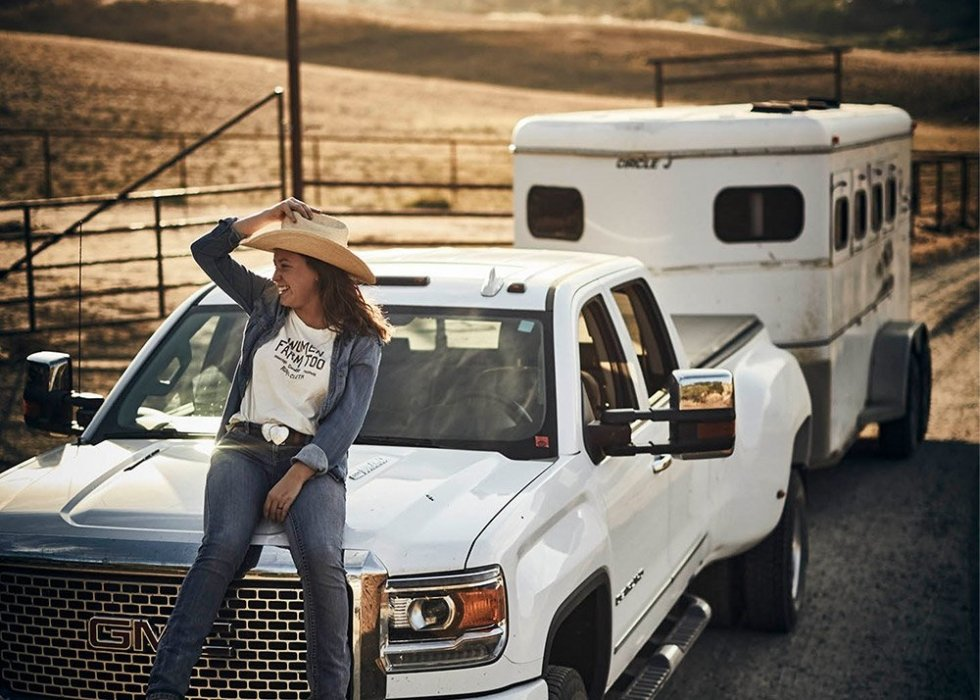 A female rancher sitting on a GMC truck with horse trailer