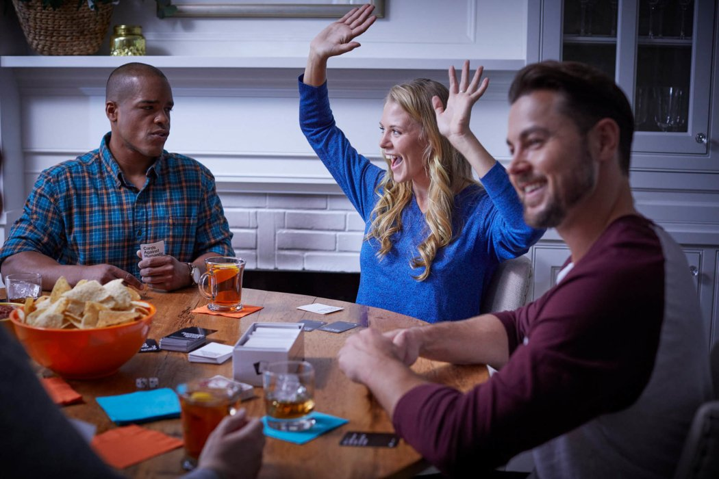 A group of people playing games at a party with blackheart rum - lifestyle drink photography