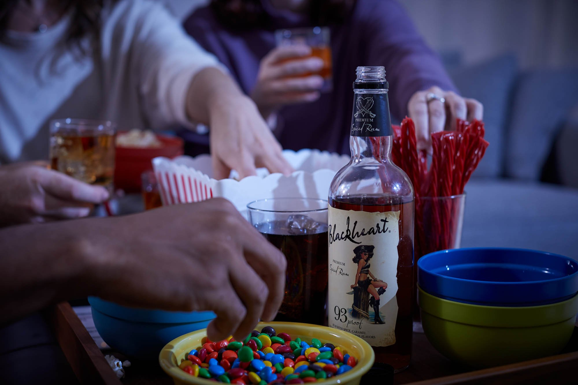 Blackheart rum on a snack table during movie night - lifestyle drink photography