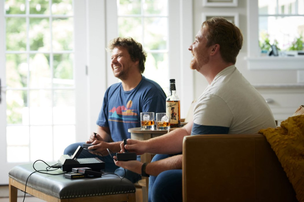 Two guys playing old school video games with blackheart rum - lifestyle drink photography