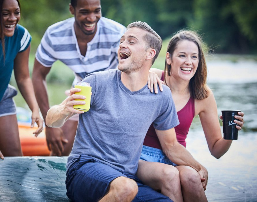 Group of young people enjoying a day on the banks of a river laughing - lifestyle drink photography