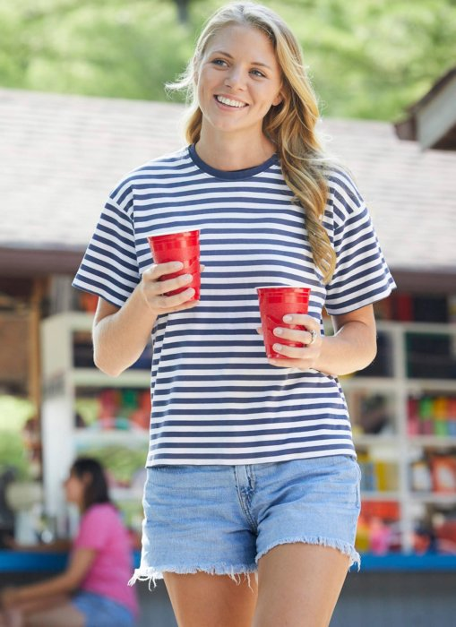 A young woman with two cups walking - - lifestyle drink photography