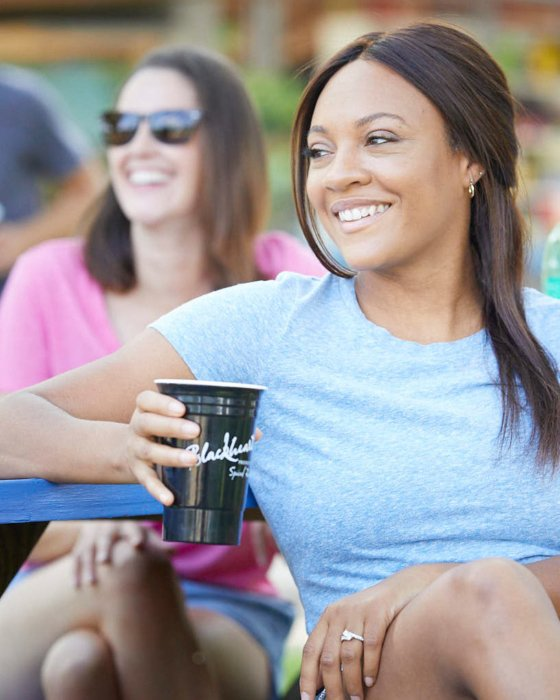 A owman at a picnic table enjoying blackheart rum - lifestyle drink photography