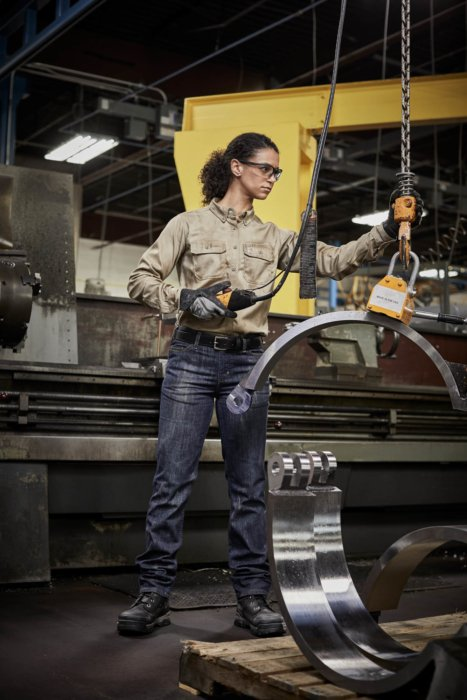 A woman operating a lift in an industrial environment - workplace photography