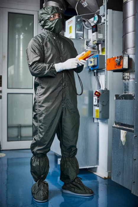A man in a green jumpsuit in a sterile environment - work apparel photography