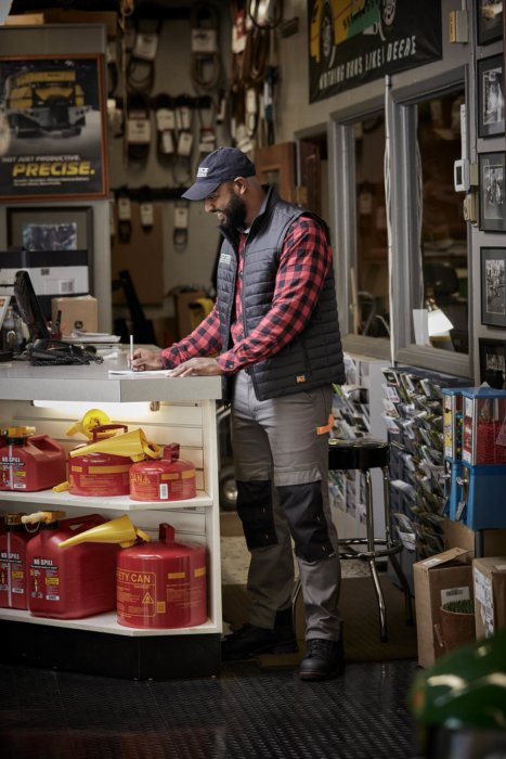 A man at a hardware store counter writing notes A man walking with equipment - work apparel photography
