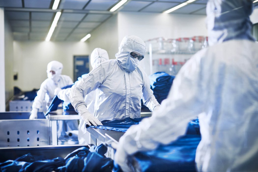 A group of workers wearing sterile clothing - A man wearing dark green sterile work clothes - work apparel photography