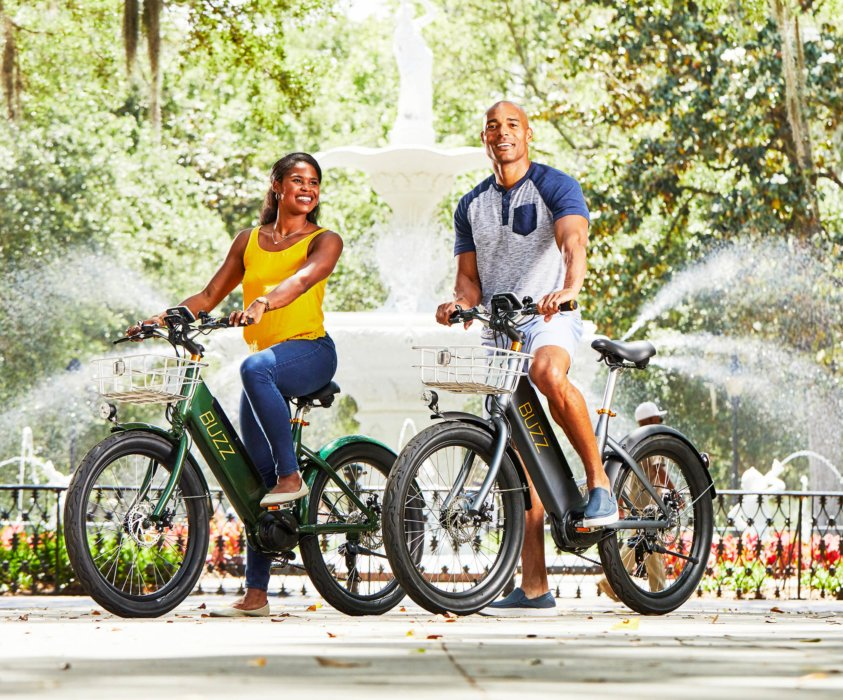 A young couple riding a electric bike in a city park - product lifestyle photography