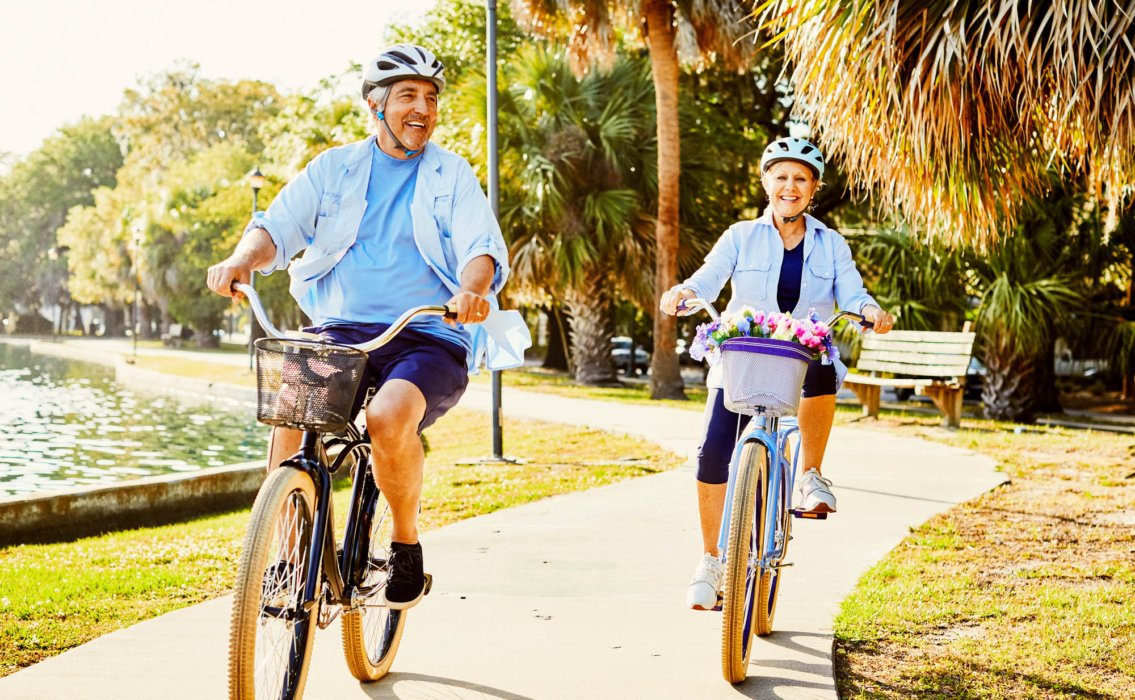 A happy elderly couple riding bikes in a city park - product lifestyle photography