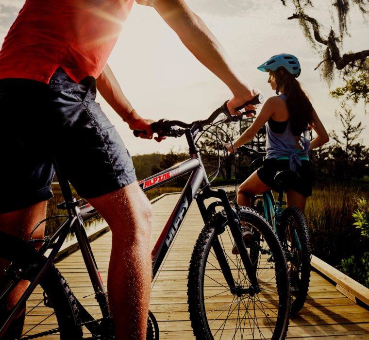 A young couple riding alpine huffy bikes on a water walk way - Royce Union - product lifestyle photography